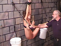 Young Nicole hangs bound to the dungeon wall and prodded with metal procurement